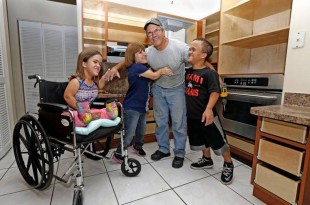 Carpenter Carlos Diaz gets a hug from Lissette Ference and her children Zach, 17, and Alannah, 13. The Ference family's kitchen cabinets were lowered with help from Wish Book readers. CHARLES TRAINOR JR MIAMI HERALD STAFF